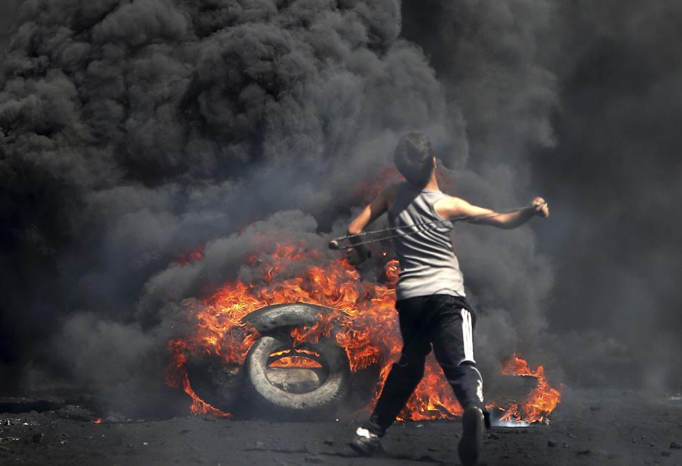 Un protestatar palestinian aruncă cu pietre înspre forţe de securitate israeliene (nu se văd în imagine) în timpul unui miting împotriva exproprierilor de pământ de către Israel, în satul Kafr Qadddum din Cisiordania, vineri, 26 septembrie 2014.