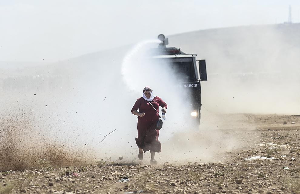 O femeie de origine kurdă fuge din faţa unui tun de apă, în timpul luptelor dintre soldaţi turci şi protestatarii kurzi în localitatea Sanliurfa aflată în apropierea graniţei Turciei cu Siria, luni, 22 septembrie 2014.