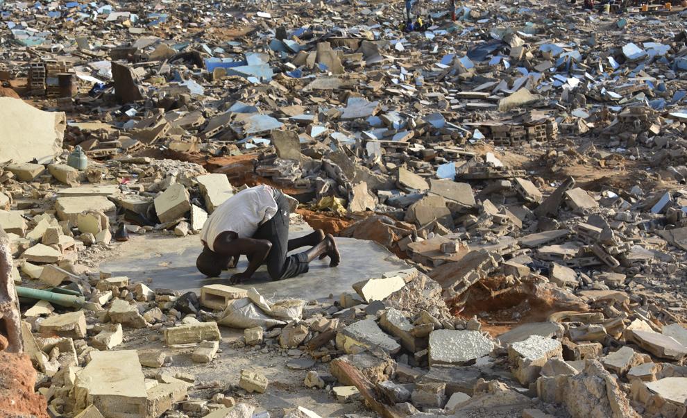 Un bărbat se roagă printre dărâmăturile caselor  demolate de autorităţi, datorită pericolului de alunecare de teren, în Abidja, Coasta de Fildeş, sâmbătă, 20 septembrie 2014.