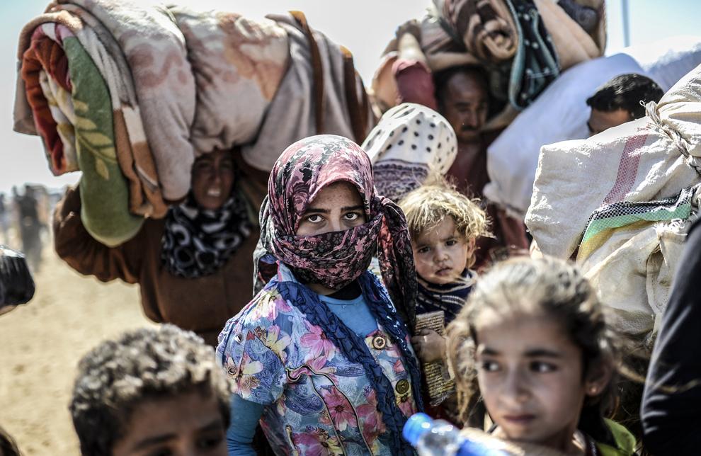 Kurzi de origine siriană îşi cară bunurile în timp ce trec graninţa dintre Siria şi Turcia, în apropierea oraşului Suruc din Turcia, marţi 23 septembrie 2014.