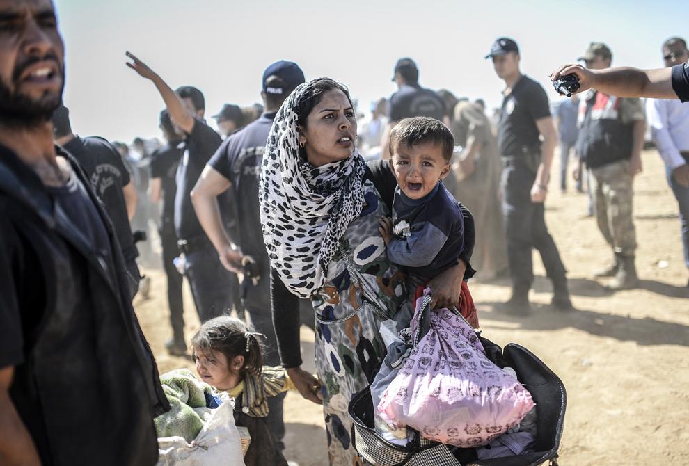 O femeie kurdă din Siria trece graninţa dintre Siria si Turcia, în apropierea oraşului Suruc din Turcia, marţi 23 septembrie 2014.