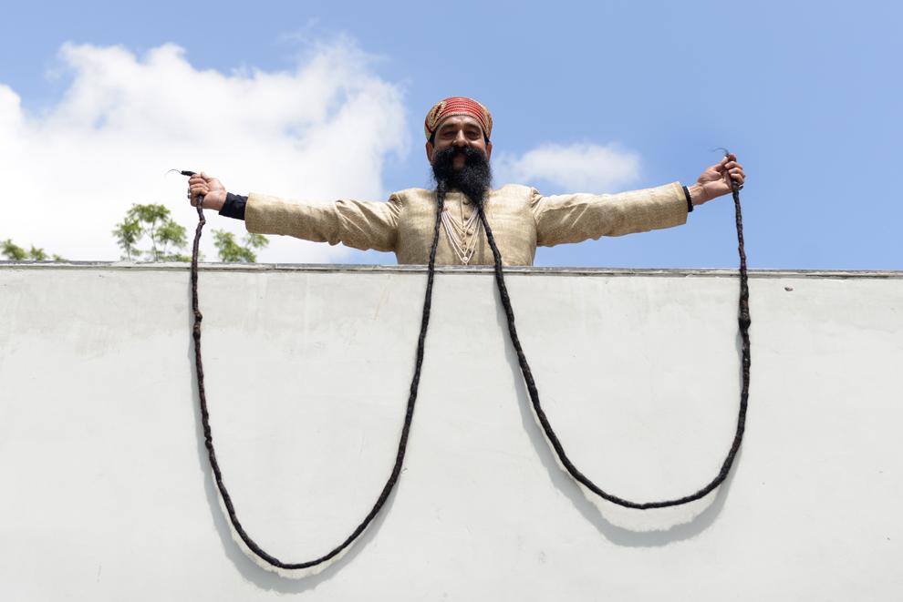 Ram Singh Chauhan îşi arată mustaţa sa de aproximativ 5 metri jumătate după ce a intrat în cartea recordurilor, în Ahmedabad, India, miercuri, 24 septembrie 2014.
