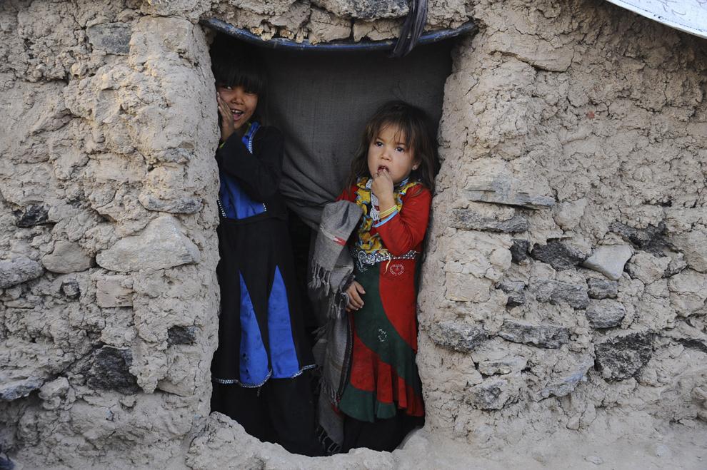 Două fetiţe refugiate stau la intrarea într-un adăpost temporar aflat la periferia provinciei Herat, Afganistan, duminică, 28 septembrie 2014.