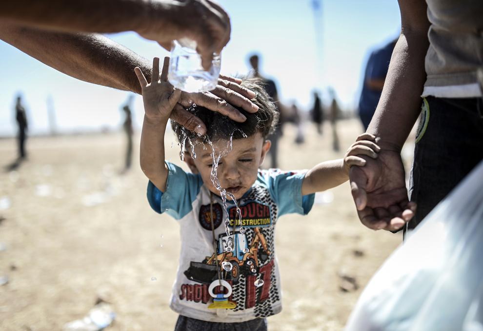 Un bărbat toarnă apă pe un copil după ce au trecut graniţa dintre Siria şi Turcia, în apropiere de oraşul sud-estic Suruc, în provincia Sanliurfa, Turcia, sâmbătă, 20 septembrie 2014.