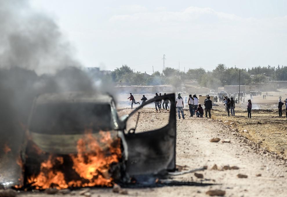 Kurzi se luptă cu soldaţi turci în apropiere de graniţa cu Siria, după ce autoritaţile turce au închis temporar graniţa, împiedicând astfel întoarcerea tinerilor în Siria, după ce şi-au acompaniat familiile, în apropiere de oraşul sud-estic Suruc, provincia Sanliurfa, luni, 22 septembrie 2014.