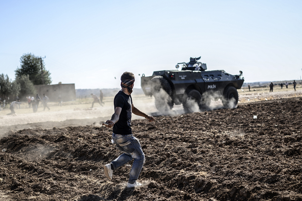 Un tânăr kurd aruncă cu pietre într-un vehicul blindat, după ce autoritaţile turce au închis temporar graniţa din oraşul sud-estic Suruc, provincia Sanliurfa, Turcia, luni, 22 septembrie 2014.