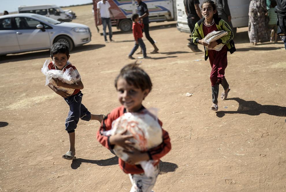Copii kurzi sirieni aleargă, după ce au primit pâine, în apropiere de graniţa cu Siria, în oraşul sud-estic Suruc, provincia Sanliurfa, Turcia, marţi, 23 septembrie 2014.