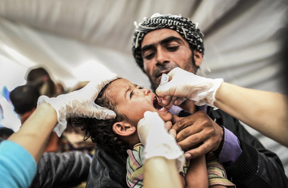 Un copil sirian este vaccinat în apropiere de graniţa cu Siria, în oraşul sud-estic Suruc, provincia Sanliurfa, Turcia, marţi, 23 septembrie 2014.