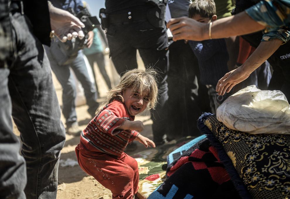 Un copil kurd sirian plânge, în timp ce poliţia turcă caută prin bagaje, după traversarea granitei Siria – Turcia, în oraşul sud-estic Suruc, provincia Sanliurfa, Turcia, marţi, 23 septembrie 2014.
