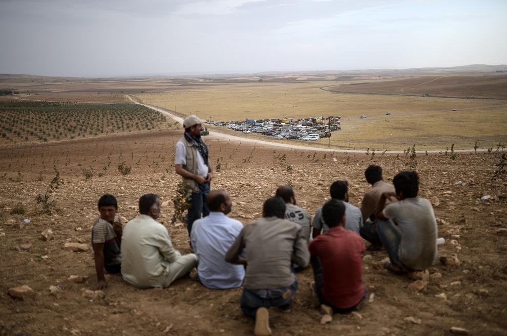 Kurzi sirieni, ce stau pe un deal, privesc luptele date între jihadiştii Statului Islamic (IS) şi luptatorii kurzi, în satul Swedi, la 10 km de Suruc, Turcia, miercuri, 24 septembrie 2014.