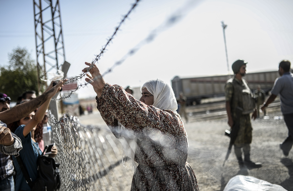 O femeie kurdă siriană se întoarce în Siria prin punctul de trecere Mursitpinar, în oraşul Suruc din provincia Sanliurfa, Turcia, miercuri, 24 septembrie 2014.