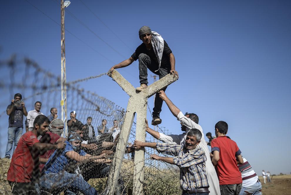 Kurzi turci şi sirieni încearcă să dărâme gardul de la graniţa dintre Turcia şi Siria, în timpul unui protest la punctul de trece a graniţei Mursitpinar, în Suruc, Sanliurfa, Turcia, vineri, 26 septembrie 2014.