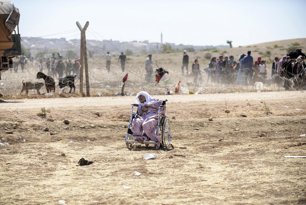 O femeie de etnie kurdă din Siria doarme în scaunul cu rotile după ce a trecut graniţa dintre Siria şi Turcia în apropiere de oraşul sud-estic Suruc, în provincia Sanliurfa, Turcia, sâmbătă, 20 septembrie 2014.