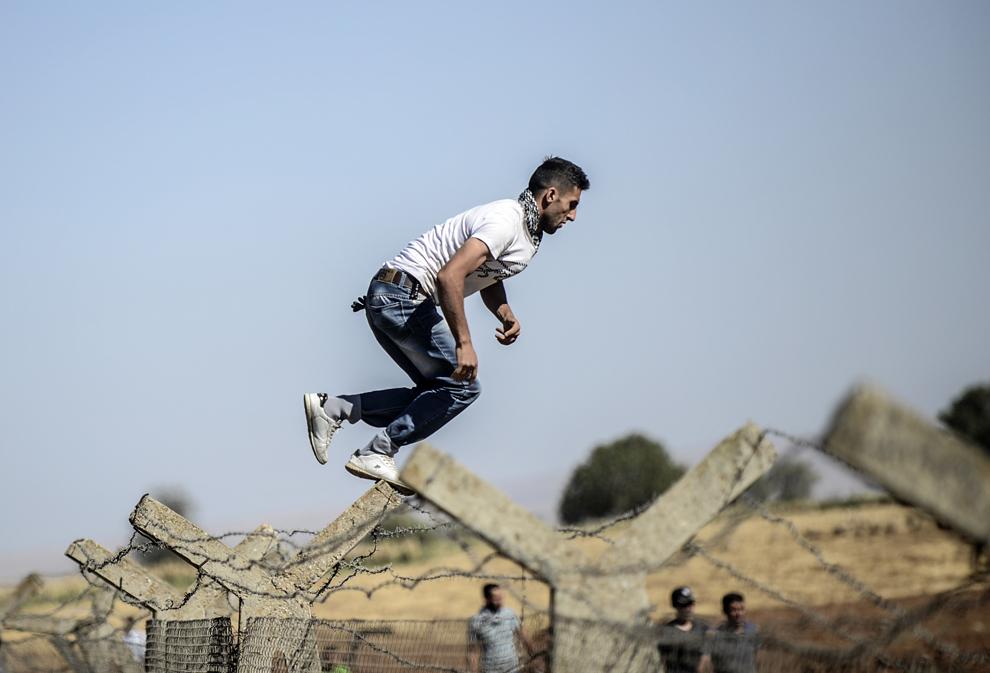 Un bărbat kurd sare peste gardul graniţei dintre Turcia şi Siria, în timpul unui protest la punctul de trecere a graniţei Mursitpinar, în Suruc, Sanliurfa, Turcia, vineri, 26 septembrie 2014.
