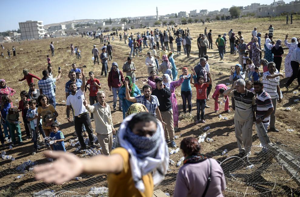 Kurzi turci şi sirieni strigă lozinci după distrugerea gardului graniţei dintre Turcia şi Siria, la punctul de trece a graniţei Mursitpinar, în Suruc, Sanliurfa, Turcia, vineri, 26 septembrie 2014.