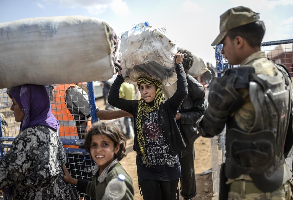 Kurzi sirieni ce fug de masacrul făcut de jihadiştii Statului Islamic (IS) , trec graniţa dintre Siria şi Turcia, în Suruc, Sanliurfa, Turcia, sâmbătă, 27 septembrie 2014.