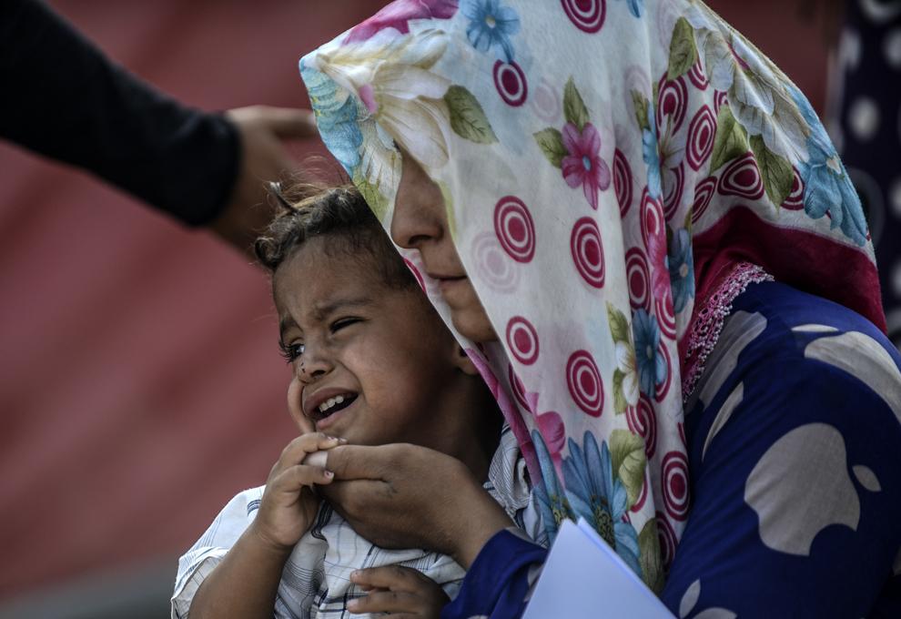 Un copil plânge în timp ce kurzi sirieni ce fug de masacrul facut de jihadiştii Statului Islamic (IS) trec graniţa dintre Siria şi Turcia, în Suruc, Sanliurfa, Turcia, sâmbătă, 27 septembrie 2014.