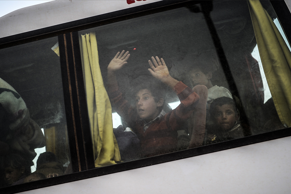 Kurzi sirieni ce fug de masacrul făcut de jihadiştii Statului Islamic (IS) stau într-un autocar, după traversarea graniţei dintre Siria şi Turcia, în Suruc, Sanliurfa, Turcia, sâmbătă, 27 septembrie 2014.