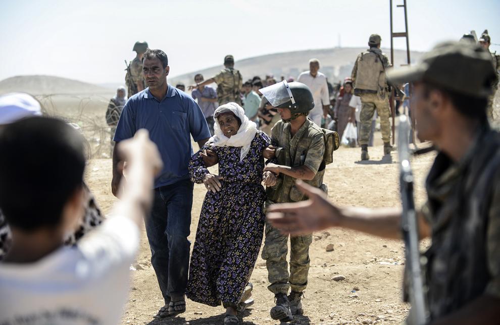 Un poliţist ajută o femeie de etnie kurdă din Siria după ce a trecut graniţa dintre Siria şi Turcia în apropiere de oraşul sud-estic Suruc, în provincia Sanliurfa, Turcia, sâmbătă, 20 septembrie 2014.