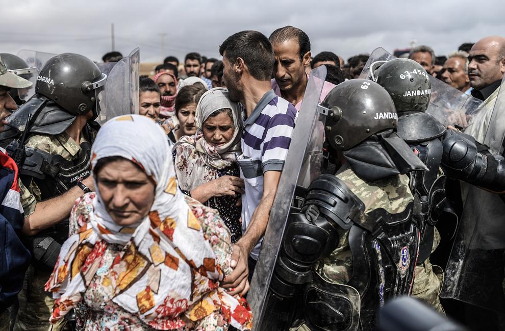 Forţe militare turce din cadrul Jandarma, blochează accesul către punctul de trecere a graniţei Mursitpinar, în apropiere de graniţa cu Siria, în timp ce kurzi sirieni încearcă să treacă printre scuturile lor, în Suruc, Sanliurfa, Turcia, duminică, 28 septembrie 2014.