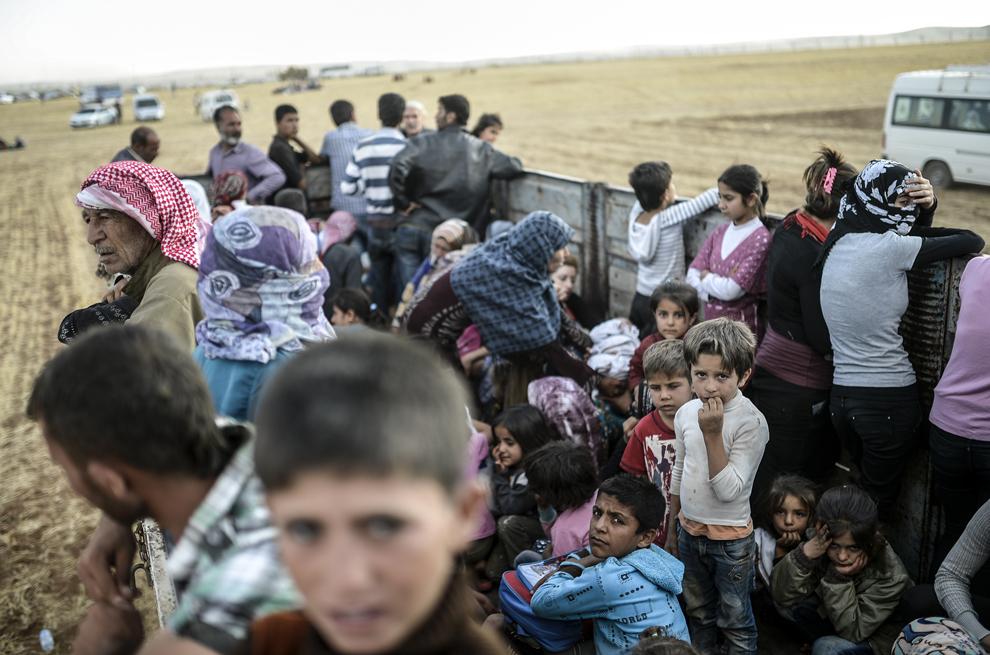 Kurzi sirieni aşteaptă într-o remorcă la graniţa cu Siria, în apropiere de oraşul sud-estic Suruc, în provincia Sanliurfa, Turcia, sâmbătă, 20 septembrie 2014.