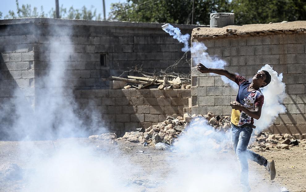 Un protestatar kurd aruncă cu o fumigenă înapoi înspre soldaţii turci, în timpul unui protest, după ce autoritatile turce au închis temporar graniţa din oraşul sud-estic Suruc, provincia Sanliurfa, Turcia, duminică, 21 septembrie 2014.