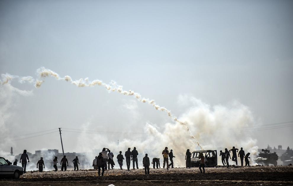 Protestatari kurzi se luptă cu soldaţi turci în apropiere de graniţa cu Siria, după ce autoritaţile turce au închis temporar graniţa din oraşul sud-estic Suruc, provincia Sanliurfa, Turcia, luni, 22 septembrie 2014.