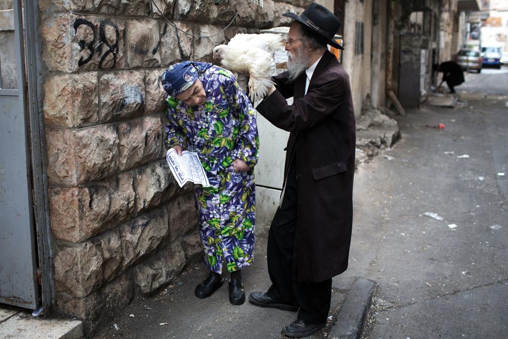Un cuplu de evrei ultra-ortodocşi în vârstă practică ceremonia Kaparot cu un pui, în cartierul ultra-ortodox Mea Shearim, în Ierusalim, joi, 2 octombrie 2014. Ritualul evreiesc ar trebui să transfere păcatele anului trecut la carnea de pui, şi este efectuat înainte de ziua Ispăşirii, sau Yom Kippur, cea mai importantă zi din calendarul evreiesc, care a început în acest an în ziua vineri, 3 octombrie, la apusul soarelui.