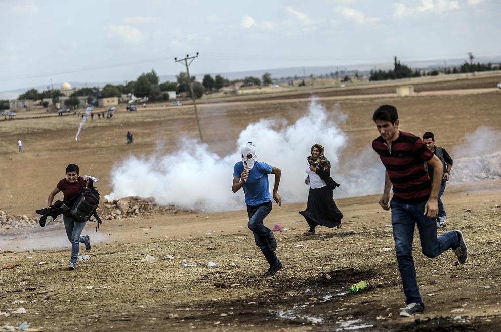 Poliţişti şi soldaţi turci, în conflict cu protestatarii, în apropiere de graniţa cu Siria, în Suruc luni, 29 septembrie 2014. Zeci de mii de sirieni kurzi se refugiază în Turcia, fugind din calea atacurilor violente ale jihadiştilor Statului Islamic (IS). Mulţi dintre refugiaţi vor acum să se întoarcă pentru a-şi proteja casele şi să se alăture luptei împotriva militanţilor IS.
