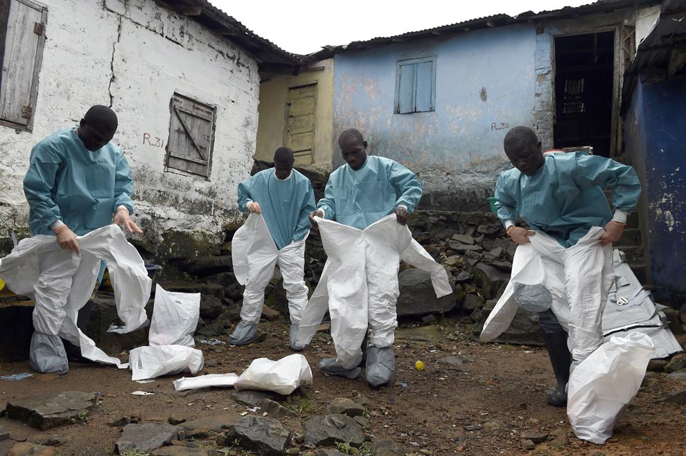 Personalul medical membru al Crucii Roşii se îmbracă cu echipament de protecţie, înainte de a colecta cadavrul unei victime a Ebola, în Monrovia, Liberia, luni, 29 septembrie 2014.