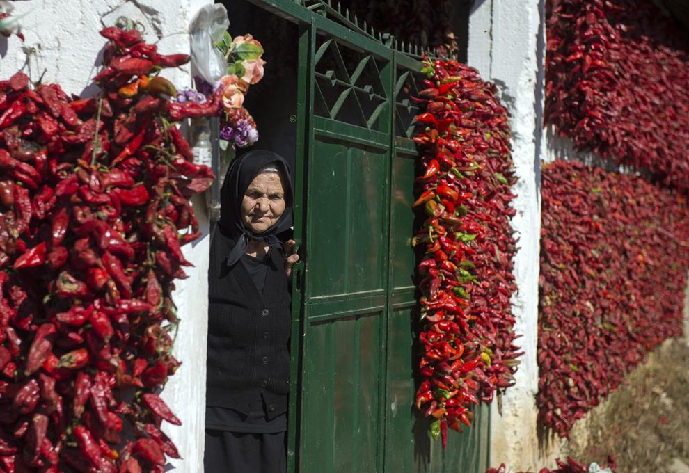 """O femeie în vârstă priveşte din poarta casei ei acoperite cu fire de boia de ardei roşu, în satul Donja Lokosnica, în apropiere de oraşul Leskovac, sudul Serbiei, miercuri,  1 octombrie 2014. Donja Lokosnica este considerată """"capitala sârbă a paprika"""", din moment ce aproape toţi cei aproximativ 1300 de locuitori se ocupă cu creşterea ardeiului iute roşu."""