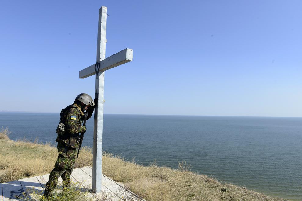 Un militar al batalionului pro-ucrainean Sfânta Maria se roagă lângă o cruce, ridicată pe malul mării,  în apropiere de oraşul estic din Ucraina, Mariupol, joi, 2 octombrie 2014.