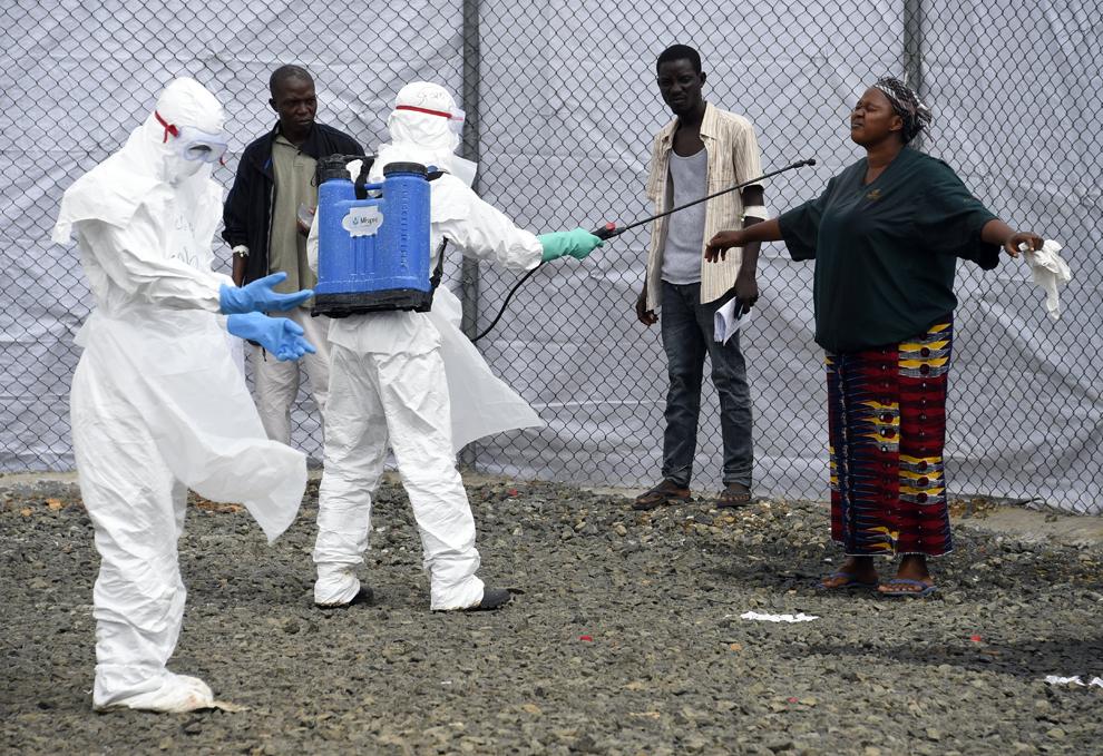 Personal medical dintr-un centru pentru tratament al bolnavilor infectaţi cu Ebola dezinfectează persoane care au adus spre îngrijire pacienţi suspecţi de a fi infectaţi cu Ebola, într-un spital din Monrovia, Liberia, joi, 2 octombrie 2014.