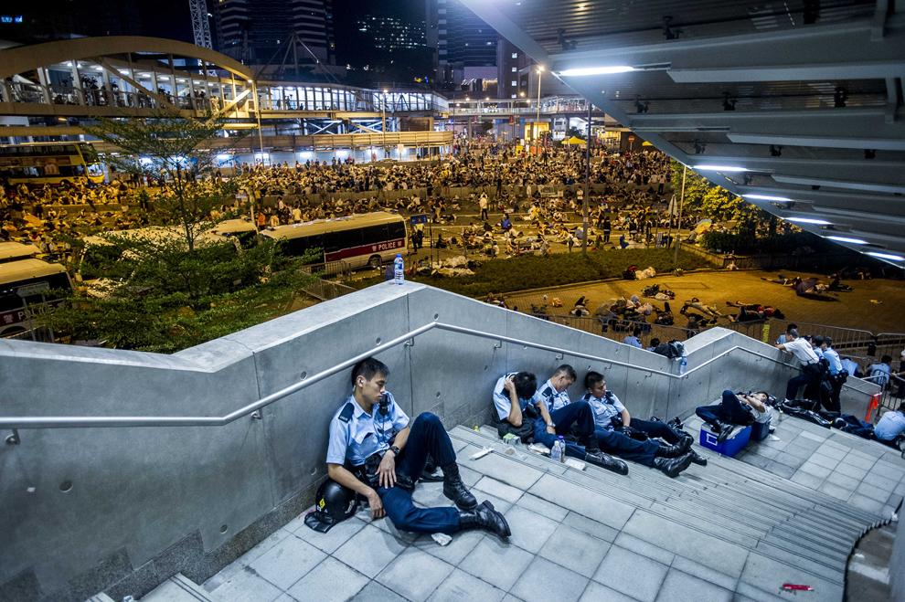 Poliţişti se odihnesc în urma protestelor pro-democraţie din Hong Kong, luni, 29 septembrie 2014.