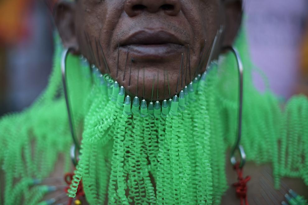 Un adept al Chinese Bang Neow Shrine, cu ace introduse în faţă, aşteaptă începerea unei procesiuni stradale în timpul Festivalului anual Vegetarian în oraşul sudic thailandez Phuket, luni, 29 septembrie 2014. În timpul festivalului, adepţii religioşi se taie cu săbii, îşi străpung obrajii cu obiecte ascuţite şi comit alte acte dureroase, în dorinţa de a se purifica, luând păcatele comunităţii asupra lor.