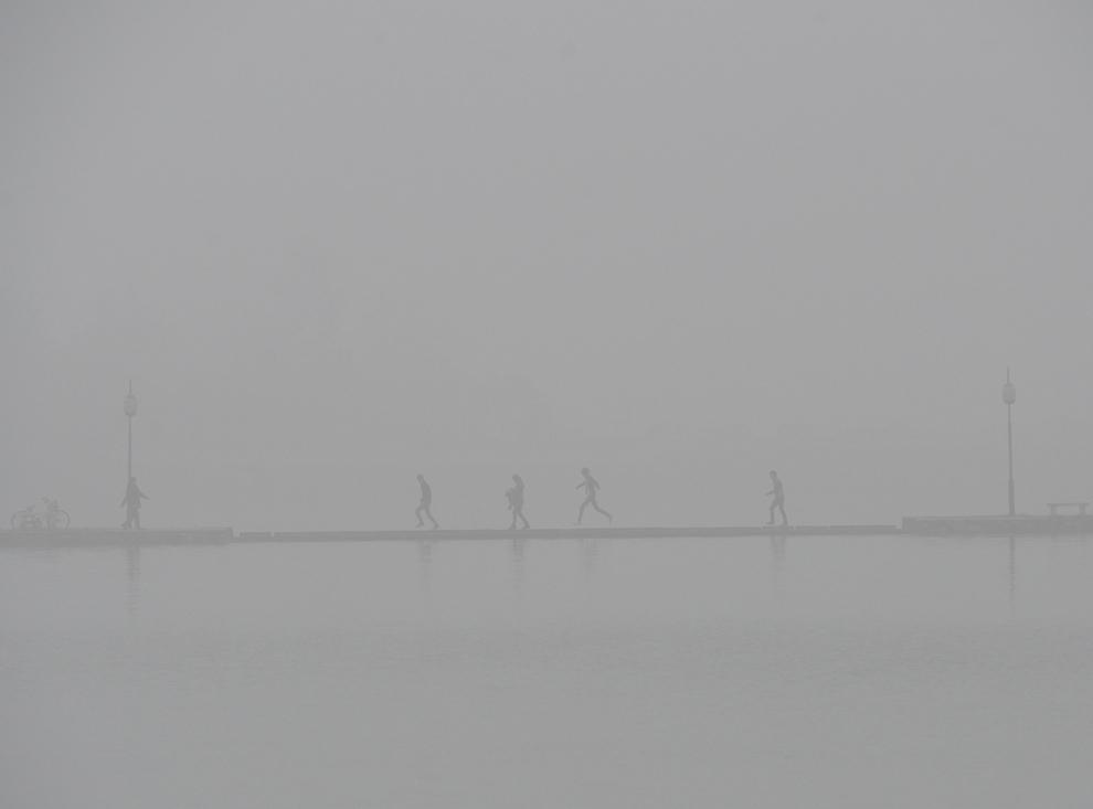 Pasageri circulă pe un pod afundat în smog, în Xiangyang , provincia Hubei, China, miercuri, 22 octombrie 2014.
