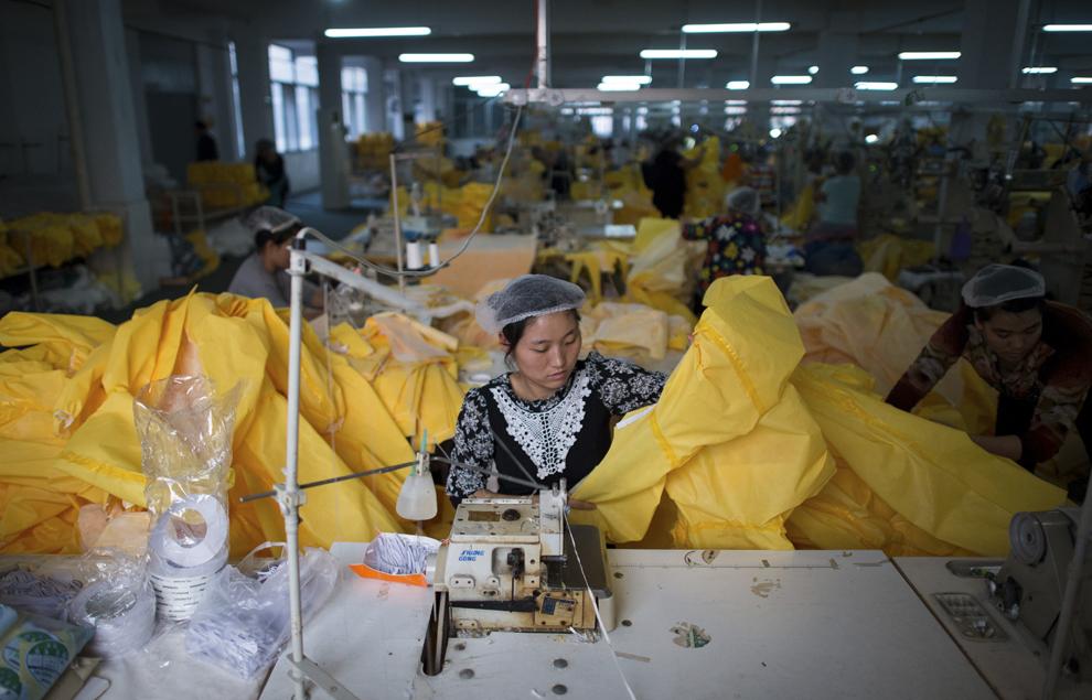 Femei  confecţionează costume de protecţie CT1SL428, create pentru protecţia voluntarilor ce se ocupă de persoanele infectate cu Ebola, în Lakeland Industries Inc., în Anqiu, 500 de km de Beijing, China, joi, 23 octombrie 2014.