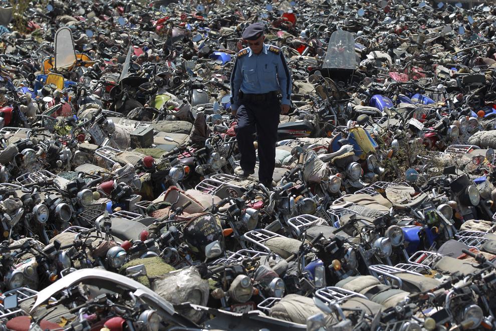 Un poliţist merge peste motociclete confiscate, după ce propietarii au încălcat o interdicţie de a merge cu motocicleta în oraş, într-o măsură creată pentru a preveni atacuri cu bombă, la sediul poliţiei din Sanaa, Yemen, luni, 20 octombrie 2014.