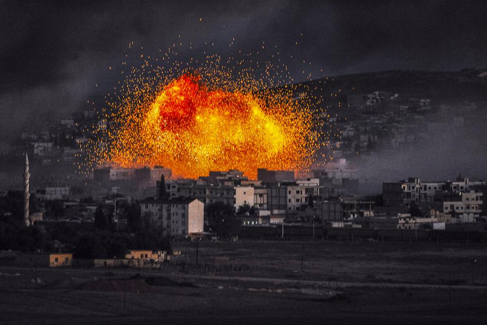 Flăcări şi fum se ridică în urma unei explozii în oraşul sirian Kobane, văzute din satul turc, Mursitpinar, provincia Sanliurfa, Turcia, luni, 20 octombrie 2014.