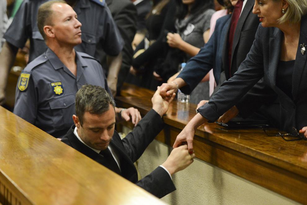 Oscar Pistorius strânge mâinile membrilor familiei, în timp ce este dus într-o celula de detenţie, după ce a fost condamnat la cinci ani de închisoare pentru uciderea prietenei sale Reeva Steenkamp, în Pretoria, Africa de Sud, marţi, 21 octombrie 2014.