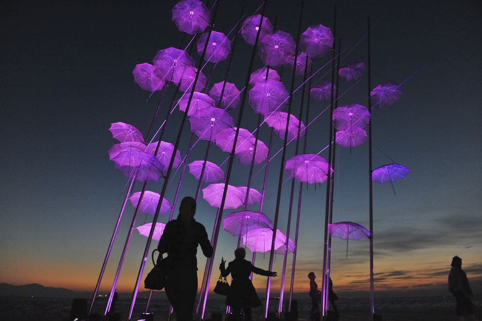"""Persoane stau în faţa unei instalaţii """"Umbrellas"""" iluminate în roz, parte a unei campanii de informare asupra cancerului la sân, în Salonic, Grecia, marţi, 21 octombrie 2014."""
