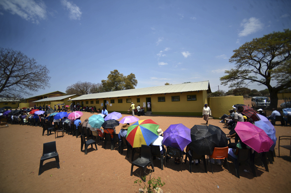 Votanţi se protejează de soare cu ajutorul umbrelelor, în timp ce stau la coadă pentru a vota, în capitala Gabone, Botswana, vineri, 24 octombrie 2014.