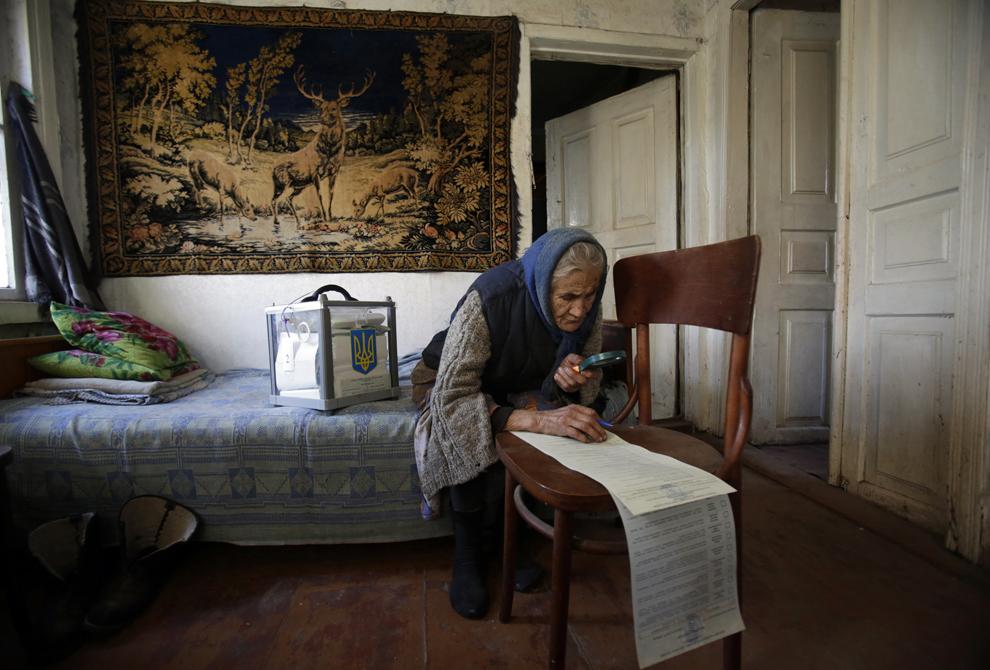 O femeie foloseşte o lupă pentru a citi buletinul de vot, în casa sa din satul Gornostaypol, aproximativ 80 de km de Kiev, duminică, 26 octombrie 2014.