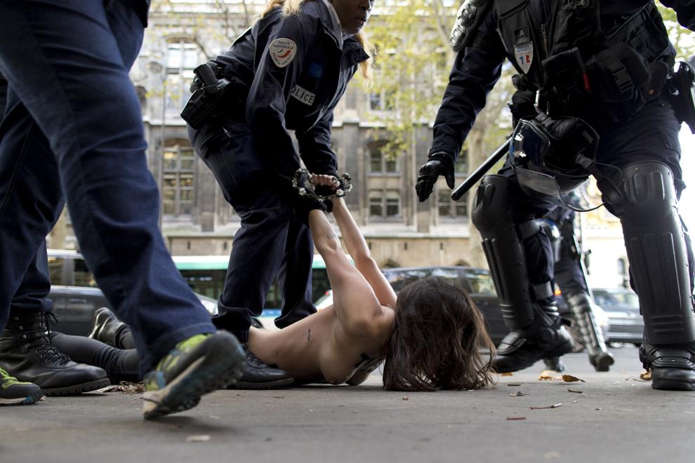 O activistă din grupul Femen este arestată în timp ce protestează topless în faţa unei judecătorii din Paris, duminică, 26 octombrie 2014.
