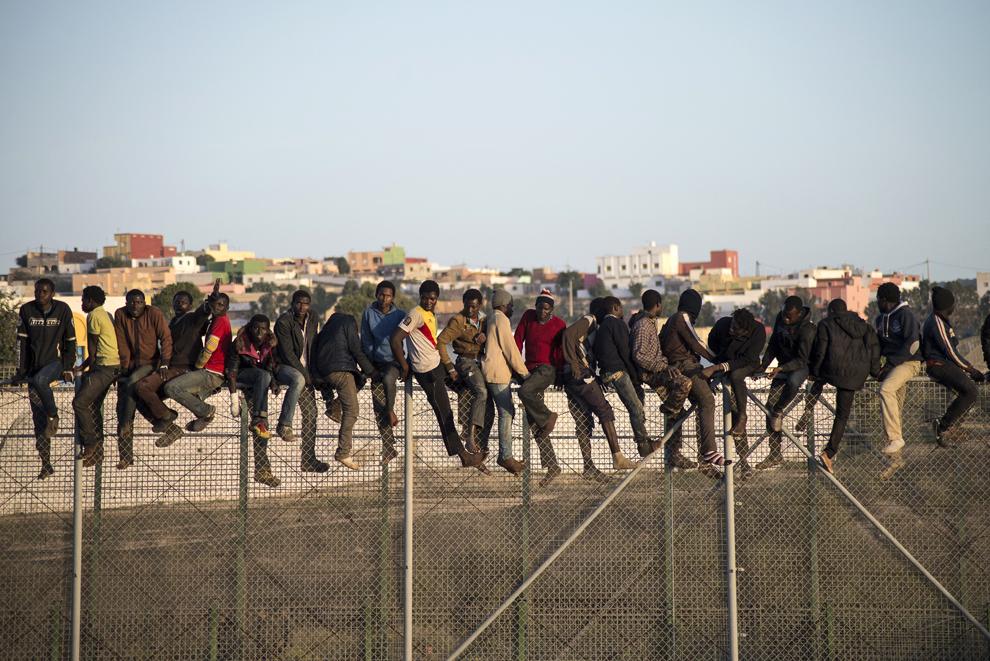 Imigranţi stau pe gardul graniţei ce separă Marocul de enclava spaniolă nord-africană Melilla, miercuri, 22 octombrie 2014.