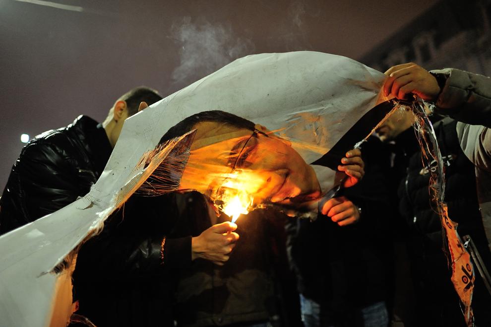Persoane dau foc unui banner cu Victor Ponta, în timpul unui miting organizat după anunţarea rezultatelor exit-poll-urilor la alegerile prezidenţiale, în Bucureşti, duminică, 16 noiembrie 2014.