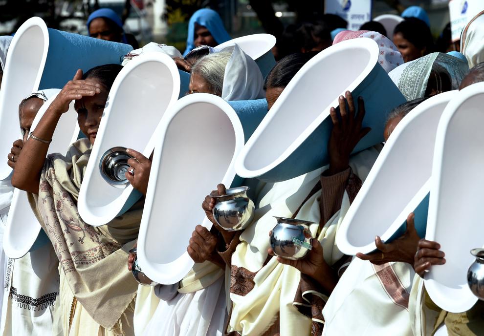 """Femei indiene ţin în braţe closete în timp ce participă la ceremonia de deschidere a festivalului internaţional """"Festivalul toaletei"""" în New Delhi, India, marţi, 18 noiembrie 2014."""