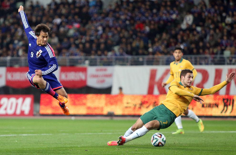 Atacantul Japoniei Shinji Okazaki (S) şutează balonul în timp ce mijlocaşul Australiei, Mathew Leckie (D) încearcă să îl blocheze, în meciul amical disputat de echipele de fotbal ale Japoniei şi Australiei,  în Osaska, marţi, 18 noiembrie 2014.