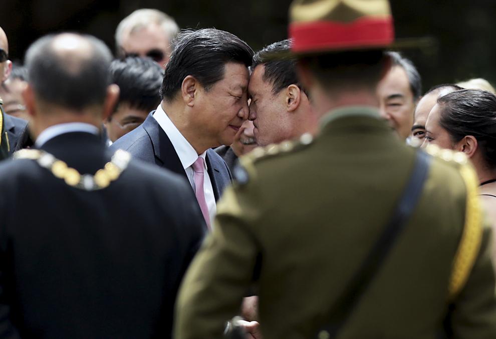 """Preşedintele Chinei, Xi Jinping (C) este salutat în mod tradiţional Maori – """"Hongi"""" de un luptator Maori în timpul unei ceremonii de primire în Wellington, Noua Zeelandă, joi, 20 noiembrie 2014."""