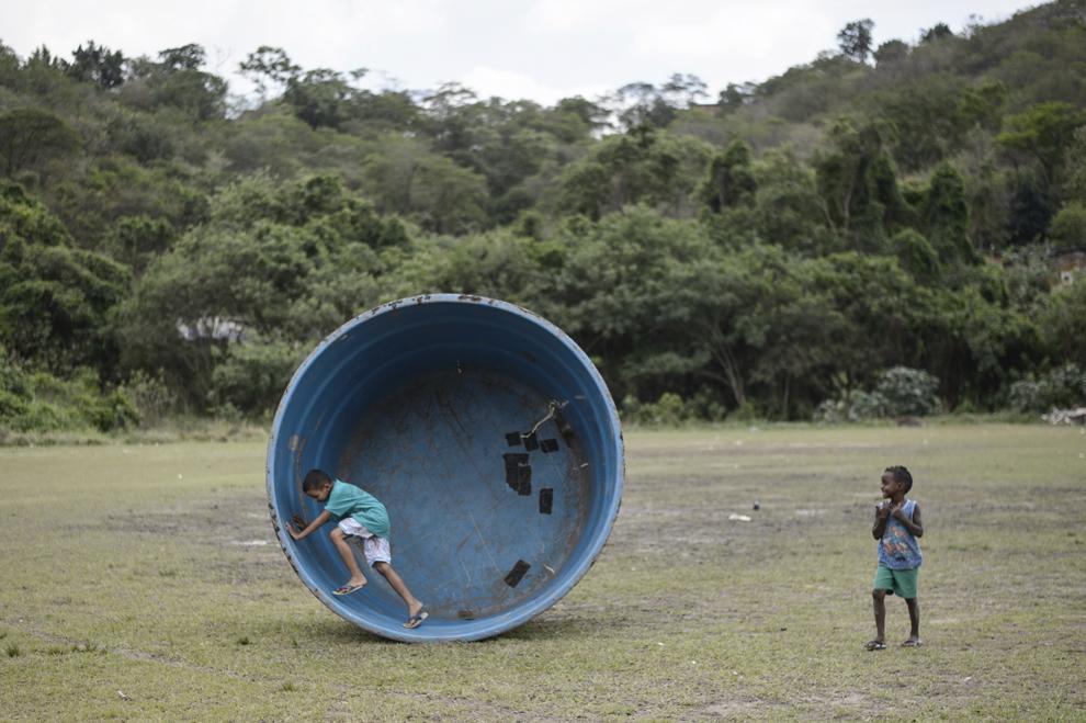 Copii se joacă într-un rezervor de apa gol aflat pe un teren de fotbal, în apropiere de favela Terra Prometida din Guadalupe, la periferia Rio de Janeiro, Brazilia, luni, 17 noiembrie 2014.